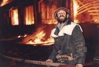 Un  uomo di fronte a una casa in fiamme.