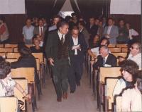 Enzo Tortora fa ingresso in una platea, seguito da un giornalista.