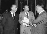 """Enzo Tortora, fra due uomini maturi (???), tiene in mano una copia del libro: """"A proposito di liberalismo - contributo per conoscerlo""""."""