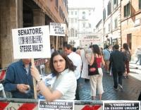 """Marianna Mascioletti (milante radicale) alza il cartello: """"Senatore, ma se suo figlio stesse male?""""), in occasione della staffetta oratoria davanti al"""