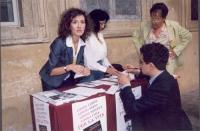 """Antonella Spolaor Dentamaro, a un tavolo radicale dove si vende il libro di Luca Coscioni """"Il Maratoneta"""". Accovacciato di fronte al tavolo: Carmelo P"""