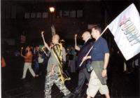 Marcia anticlericale. Marco Pannella sfila accanto a un manifestante che reca la bandiera del FUORI!