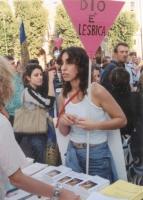 """Manifestazione e comizio anticlericale davanti a porta Pia. Una militante inalbera il cartello: """"Dio è lesbica""""."""