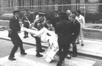 la polizia trascina via un militante radicale sdraiato sulla strada davanti al Parlamento belga per chiedere azioni legislative a favore della battagl