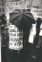"""""""Marcia di Pasqua '83. Manifestante coperto da un ombrello con cartello al collo """"""""Per la qualità della vita salviamo la vita Ass. Rad. Ecologista"""""""" ("""