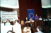 "Sala da convegno. I radicali sollevano lo striscione: ""Freedom for M. Maragakis - for the right to conscientious objection - objection in Greece""."