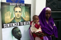 Amina (condannata a morte per adulterio in Nigeria) accanto al manifesto dell'associazione Nessuno Tocchi Caino.