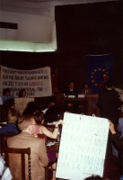 """In una sala da convegno, i radicali alzano i cartelli: """"Freedom for Magarakis - for the right to conscientious objection in Greece"""". In primo piano, s"""