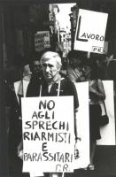 """""""Ildo Santori con un cartello al collo: """"""""No agli sprechi riarmisti e parassitari PR"""""""" durante una manifestazione. (BN)"""""""