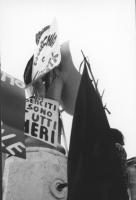 """3a marcia antimilitarista Milano-Vicenza. Fontana """"addobbata"""" con i cartelli: """"Gli esercito sono tutti neri"""", """"Anarchia e libertà""""."""