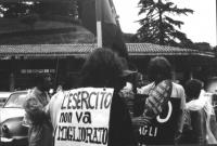 """3a marcia antimilitarista Milano-Vicenza. Marciatori indossano cartelli antimilitaristi. """"L'esercito non va migliorato..."""", """"Dans ce moment un objecte"""