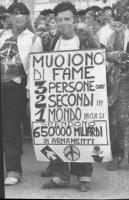"""""""Renè Andreani con al collo cartellone: """"""""muoiono di fame 3 persone ogni 2 secondi in 1 mondo in cui si spendono 650.000 miliardi in  armamenti"""""""" (BN)"""