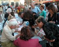 Un tavolo dove si raccolgono firme sui referendum in materia di fecondazione assistita, assediato da cittadini romani. Altre digitali.