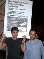 """Alessandro Gerardi e Massimiliano Iervolino, militanti radicali, sollevano il cartellone: """"Referendum sulla fecondazione assistita"""", durante un tavolo"""