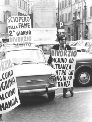 """""""Piazza Montecitorio. Roberto Cicciomessere tiene al collo cartello: """"""""divorzio. Digiuno ad oltranza contro chi mangia ad oltranza"""""""", """"""""sciopero della"""