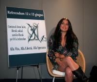 """La cantante Mietta posa accanto al cartello del """"Comitato di donne laiche"""" per il sì ai referendum sulla procreazione assistita."""