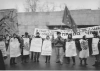manifestazione antimilitarista con radicali che portano cartelli al collo in cirillico, una bandiera UE e logo PR. (BN)