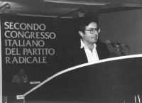 ritratto di Roberto Cicciomessere che parla dalla tribuna di un congresso italiano del PR (BN)