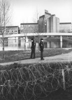 due poliziotti davanti al filo spinato, sullo sfondo laghetto ed edifici moderni. (BN) significativa