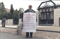 """""""Giordano Falzoni manifesta con cartello al collo davanti d'ambasciata inglese a Roma. Cartello in esperanto: """"""""respektuvi la samseksaman kulturon kie"""